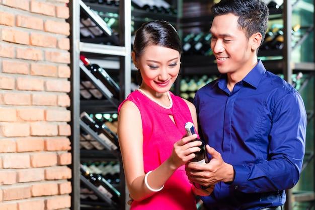 Il vino asiatico della tenuta delle coppie imbottiglia il ristorante Foto Premium
