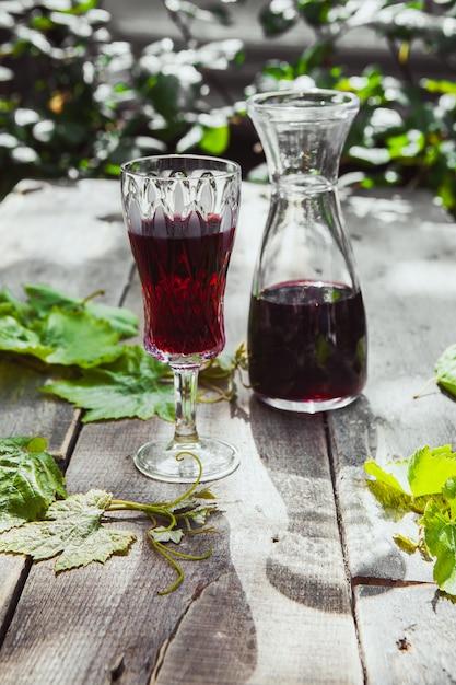 Il vino rosso con l'uva va in brocca e vetro sulla tavola delle piante e di legno, vista dell'angolo alto. Foto Gratuite