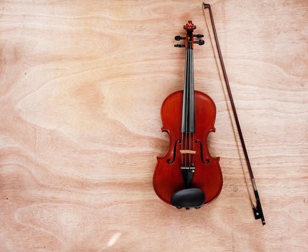 Il violino e l'arco classici messi su tavola di legno Foto Premium
