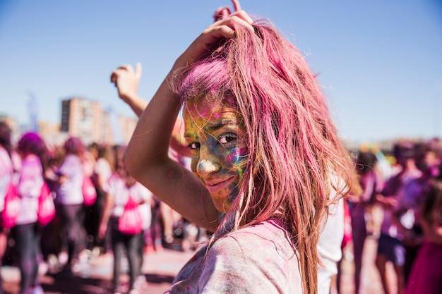 Il viso della giovane donna coperto di polvere di holi che guarda l'obbiettivo Foto Gratuite
