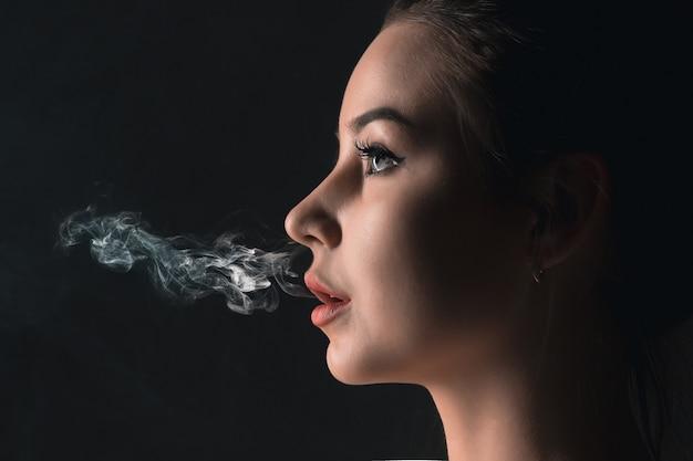 Il volto di svapare giovane donna in studio nero Foto Gratuite