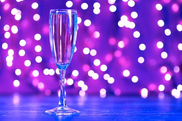 Illuminazioni natalizie e bicchiere di champagne Foto Premium