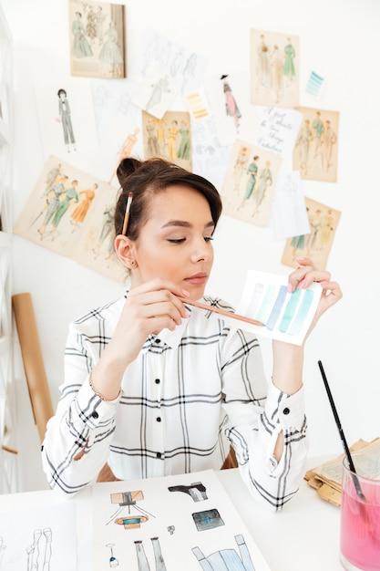 Illustratore concentrato di modo della donna che si siede alla tabella. Foto Gratuite