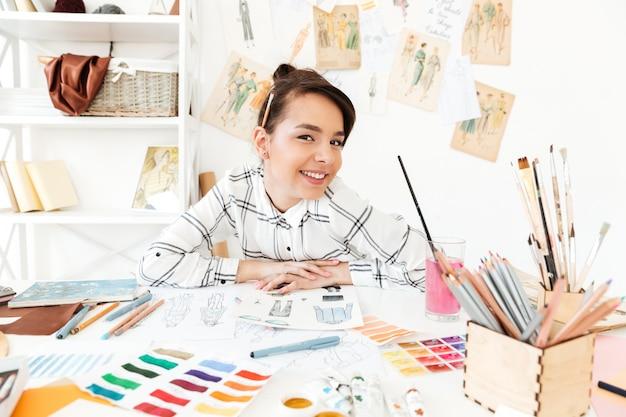 Illustratore di moda donna felice seduto al tavolo Foto Gratuite