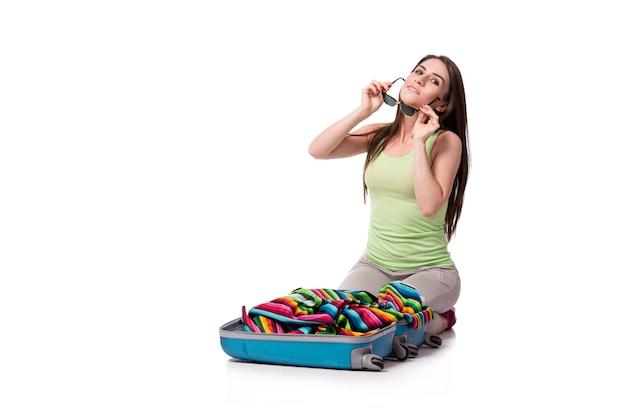 Imballaggio della donna che prepara per le vacanze estive isolate su bianco Foto Premium
