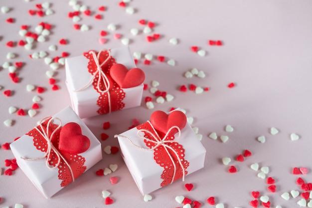 Imballaggio regali di san valentino. scatole regalo e decorazioni fatte a mano. su sfondo rosa con granelli. vista dall'alto. Foto Premium