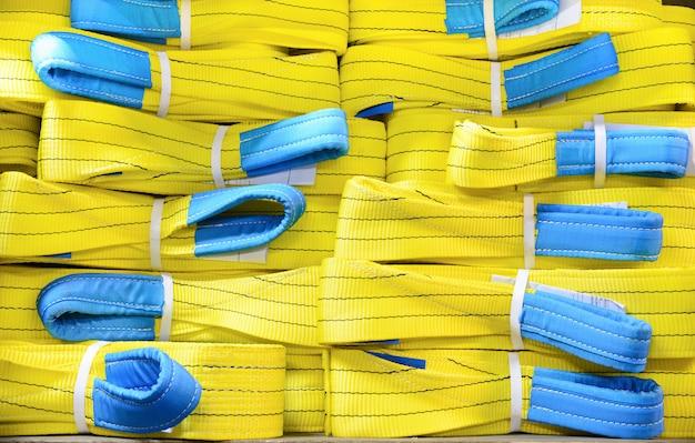 Imbragature di sollevamento morbide in nylon giallo impilate in pile. Foto Premium