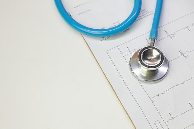 Immagine alta vicina del grafico dell'elettrocardiografia e degli stetoscopi blu. Foto Premium