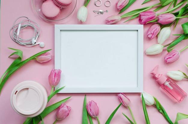 Immagine bianca con la tazza di caffè, i fiori del tulipano della molla e i macarons rosa sul fondo pastello di vista del piano d'appoggio Foto Premium