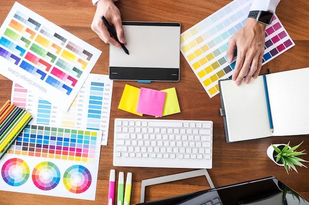 Immagine del designer grafico creativo che lavora alla selezione dei colori e al disegno sulla tavoletta grafica sul posto di lavoro Foto Premium