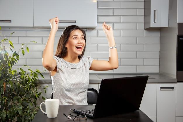 Immagine del giovane imprenditore femminile che utilizza un computer portatile mentre sollevando le mani e celebrando il suo successo Foto Premium