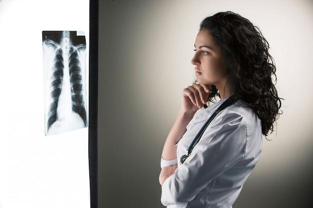 Immagine del medico attraente della donna che esamina i risultati dei raggi x Foto Gratuite