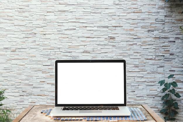Immagine del modello del computer portatile con lo schermo bianco in bianco sulla tavola di legno con la parete Foto Premium