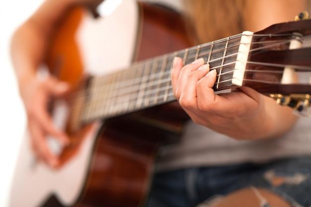 Immagine del primo piano della chitarra in mani della donna Foto Gratuite