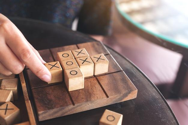 Immagine del primo piano di persone che giocano in legno tic tac toe gioco o gioco ox Foto Premium