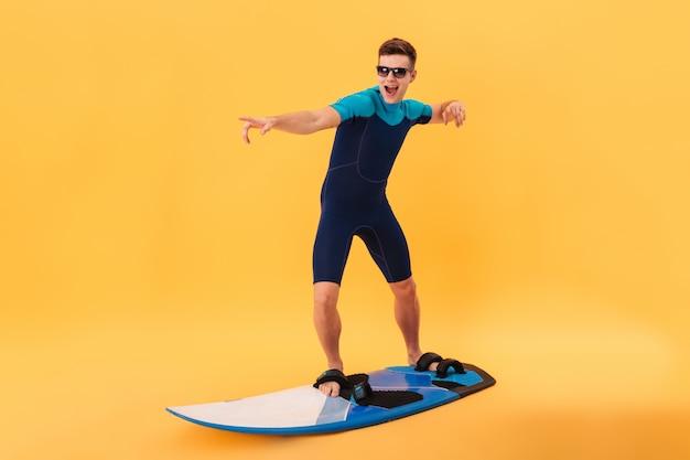 Immagine del surfista felice in muta e occhiali da sole usando la tavola da surf come sull'onda Foto Gratuite