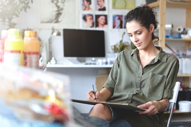 Immagine del talentuoso designer di giovane donna professionale in camicia di colore kaki seduto nel suo laboratorio, schizzi, lavorando sul design della nuova collezione di gioielli, guardando concentrato e concentrato Foto Gratuite