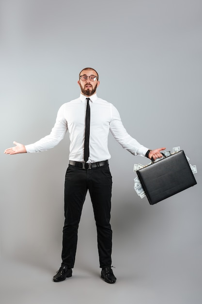Immagine dell'imprenditore uomo perplesso in bicchieri e tailleur vomitare le mani con il diplomatico pieno di soldi del dollaro, isolato sul muro grigio Foto Premium