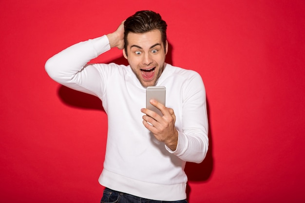 Immagine dell'uomo felice sorpreso in maglione che esamina smartphone sopra la parete rossa Foto Gratuite
