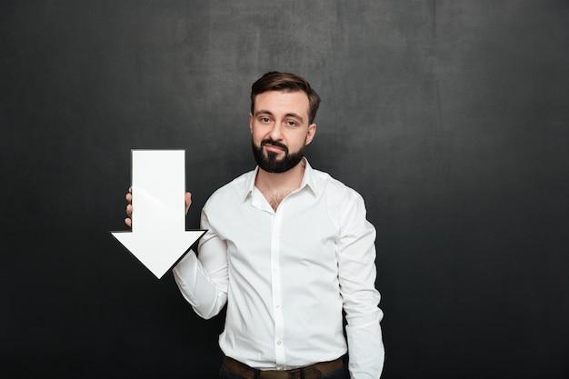 Immagine dell'uomo turbato pessimistico 30s che tiene il puntatore a freccia in bianco di discorso che dirige verso il basso sopra lo spazio grigio scuro della copia della parete Foto Gratuite