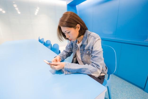 Immagine della giovane signora che per mezzo dello smartphone al co-lavoro Foto Premium
