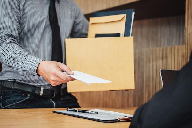 Immagine della scatola di cartone della tenuta della mano dell'uomo d'affari e dell'invio della lettera di dimissioni Foto Premium