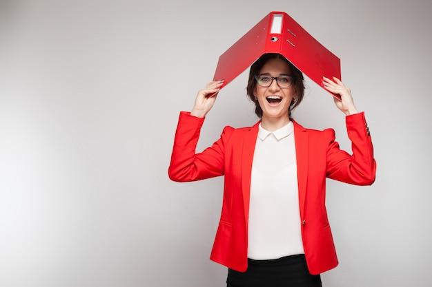 Immagine di bella donna in giacca rossa in piedi e scherzare con i documenti Foto Premium