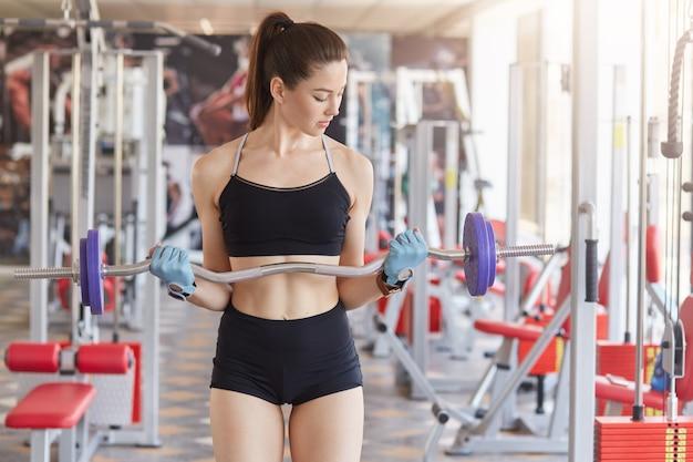 Immagine di giovane ragazza di atletica leggera allenamento duro con bilanciere in palestra. Foto Premium