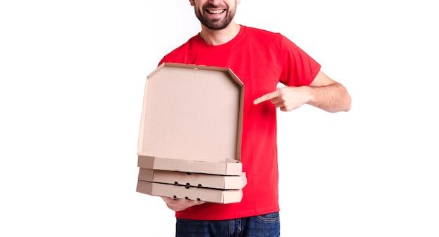 Immagine di un giovane uomo di consegna che mostra scatole per pizza Foto Gratuite
