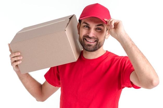 Immagine di un giovane uomo di consegna che tiene la scatola e il cappuccio Foto Gratuite