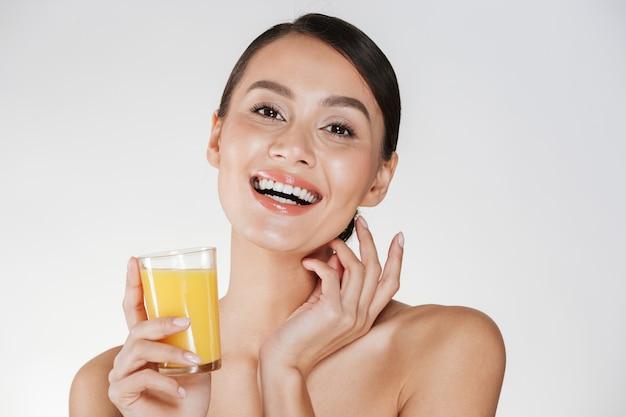 Immagine felice di signora mezza nuda che sorride e che beve il succo d'arancia appena spremuto da vetro trasparente, isolata sopra la parete bianca Foto Gratuite
