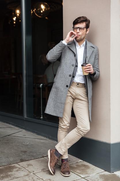 Immagine integrale dell'uomo d'affari in occhiali e cappotto Foto Gratuite