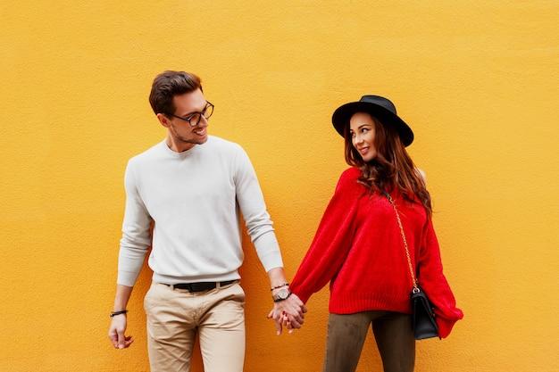 Immagine luminosa di amanti in posa sulla parete gialla. aspetto alla moda. umore romantico. tenersi per mano. giovane donna con candido sorriso che flirta con il suo fidanzato. borsa di lusso Foto Gratuite