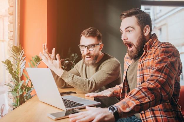 Immagine molto emotiva di ragazzi che guardano allo schermo del laptop. uno di loro è molto sorpreso e ha spalancato la bocca mentre un altro sta solo guardando lo schermo. Foto Premium