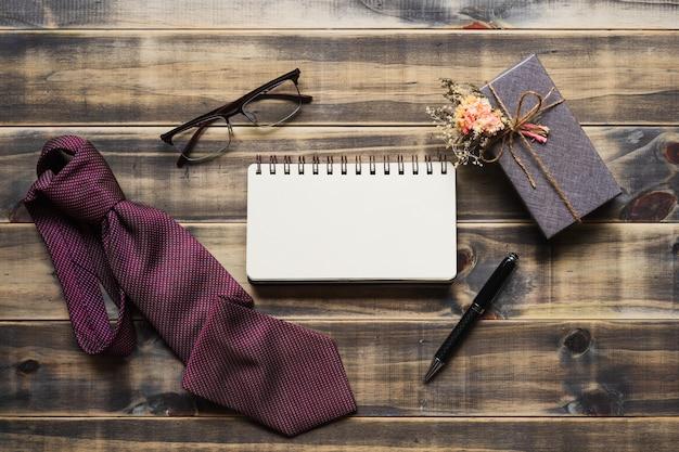 Immagine piatta laici di confezione regalo, cravatta, occhiali e taccuino spazio vuoto. Foto Premium