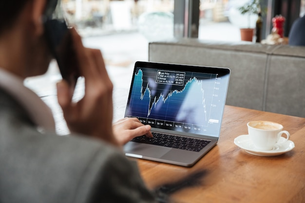 Immagine potata dell'uomo d'affari che si siede dalla tavola in caffè e che analizza gli indicatori sul computer portatile mentre parlando dallo smartphone Foto Gratuite