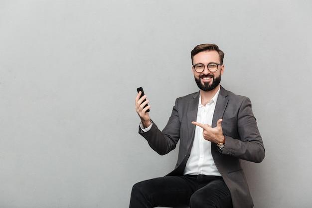 Immagine potata dell'uomo felice in occhiali che guardano sulla macchina fotografica mentre sedendosi sulla sedia e indicando sul suo telefono cellulare, isolata sopra grey Foto Gratuite