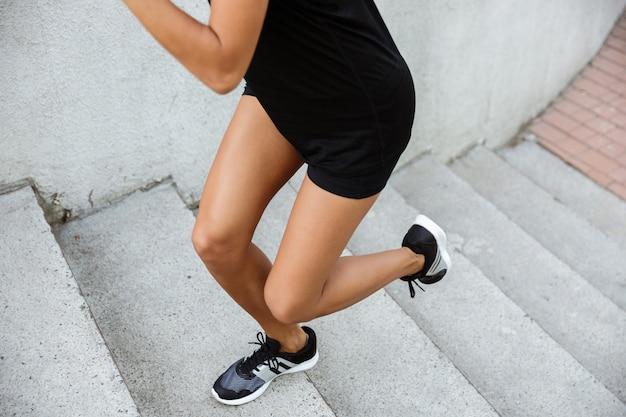 Immagine potata di una donna di forma fisica che corre su per le scale Foto Gratuite