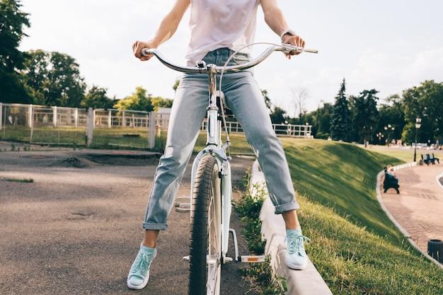 Immagine potata di una donna in jeans e una maglietta che si siede su una bicicletta della città in un parco Foto Premium