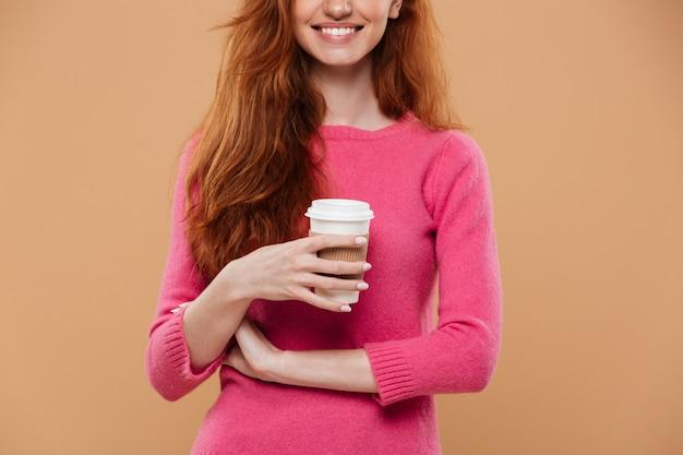 Immagine potata di una tazza di caffè sorridente della tenuta della ragazza della testarossa Foto Gratuite