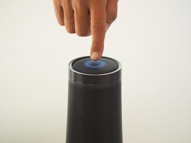 Immagine ritagliata di un uomo che utilizza un altoparlante con assistente vocale di intelligenza artificiale e tecnologia touch. Foto Premium