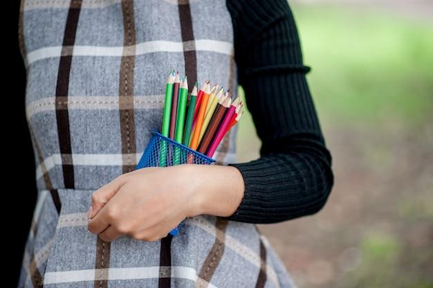 Immagini di mano e matita, colore di sfondo verde concetto di educazione Foto Premium