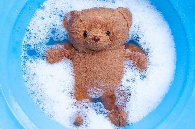 Immergere l'orso giocattolo nella dissoluzione dell'acqua detergente per bucato prima del lavaggio. Foto Premium