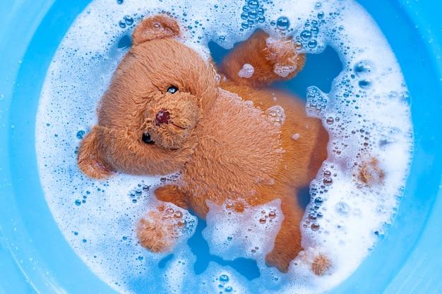Immergere l'orso giocattolo nella dissoluzione dell'acqua detergente per bucato prima era Foto Premium