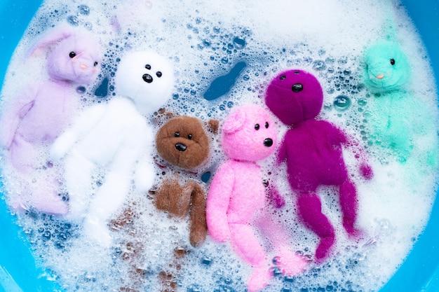 Immergi le bambole di coniglio con i giocattoli dell'orso nella dissoluzione dell'acqua del detersivo per bucato prima del lavaggio. concetto di lavanderia Foto Premium