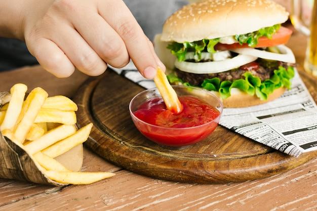 Immersione della mano del primo piano dell'angolo alto frigge con l'hamburger Foto Gratuite