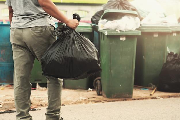 Immondizia della tenuta della mano della donna in borsa nera per la pulizia dentro per spazzare Foto Premium