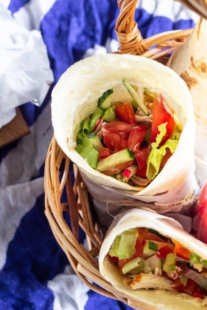 Impacchi di tortilla con pollo arrosto e verdure, succhi di frutta, verdure e frutti di bosco, baguette e formaggio. Foto Premium