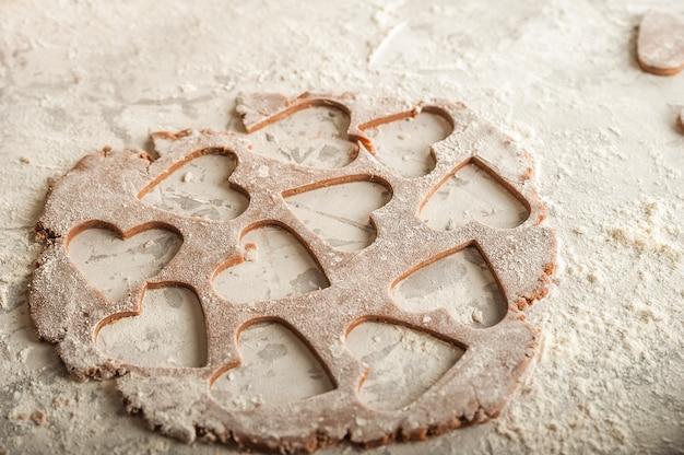 Impasto a cuore piatto con farina. texture di pasta per biscotti close-up. pasta di pan di zenzero il 14 febbraio, farina, mattarello e copia spazio. Foto Premium
