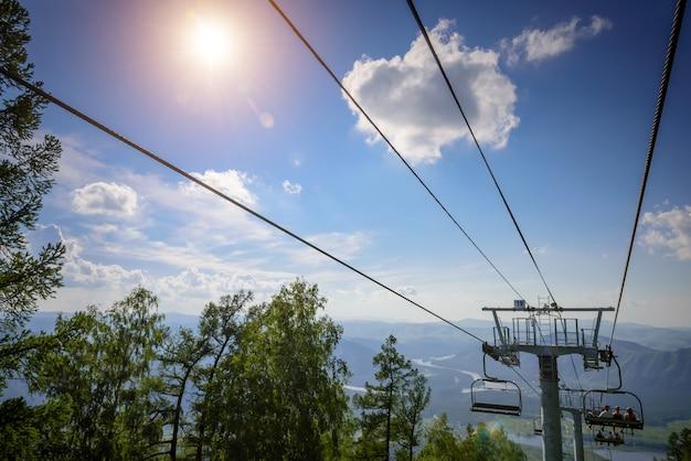 Impianti di risalita in montagna in giornata di sole contro il cielo blu, nuvole bianche, verdi colline e lago di montagna. valle della montagna con funivia, vista dall'alto. stazione sciistica in estate. Foto Premium